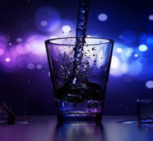 stroom water in glas met waterdruppels